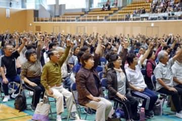 童謡を歌いながらゆっくり腕の上下運動をする参加者=いちき串木野市総合体育館