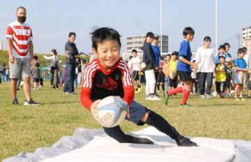 トライを決める体験参加の子ども=10月27日、岡山市の百間川河川敷グラウンド