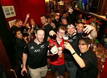 試合終了後、観戦客は夜の街へ。国籍を超えてビール片手に盛り上がった=10月3日未明、大分市中央町