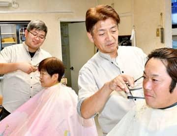 全国大会で2年連続で準優勝した庄司俊也さん(右から2人目)。左奥は長男俊樹さん=河北町・ヘアーサロン トシヤ