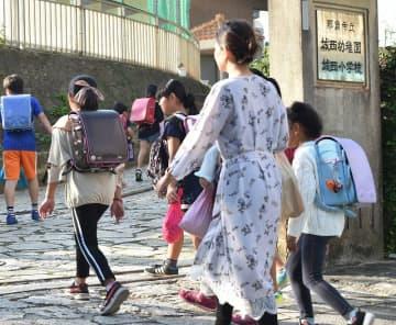 保護者と一緒に登校する城西小学校の児童ら=10月31日午前8時半すぎ、那覇市首里真和志町