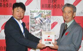 田村会長に善意を手渡す岡村さん(左)