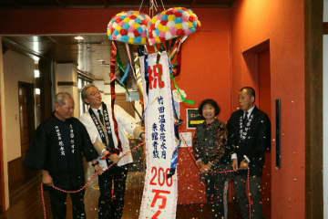 200万人目になった足立貞美さん(右から2人目)を祝う首藤勝次市長(同3人目)=竹田市会々