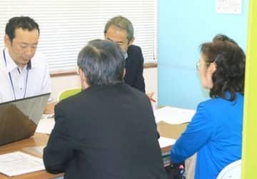 真備船穂商工会内のブースで県職員らに申請書類を確認する被災事業者(手前)=10月30日