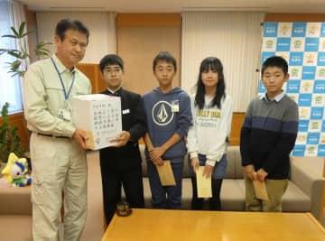 田中市長(左)に義援金を手渡す長生村立4小中学校の児童生徒代表=5日、茂原市役所