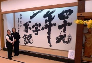 長寺に依頼され大床の間に掲げられた「四十九年一字不説」の書の前に立つ金澤さん(左)と母親の泰子さん=2017年、鎌倉・建長寺