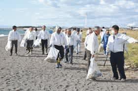 砂浜のごみを拾い集めるRCメンバー