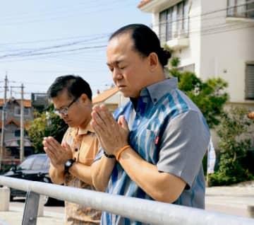 首里城のある方向に向かって祈りをささげた(右から)和多エリックさんと金城ノーマンさん=5日、那覇市の龍潭池
