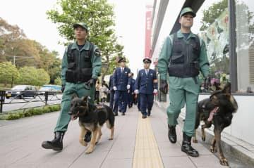 パレードのコース沿道で警視庁の警備犬を使って不審物の捜索をする警察官=7日午後、東京都港区