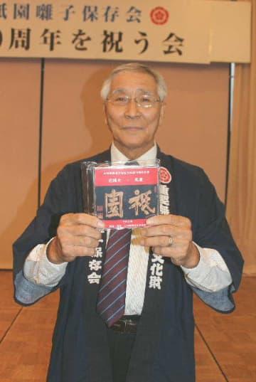 「日田の伝統芸能を後世に残したい」と話す日田祇園囃子保存会の小松史郎会長。歴史を振り返った記念冊子も200冊作製=日田市隈のみくまホテル