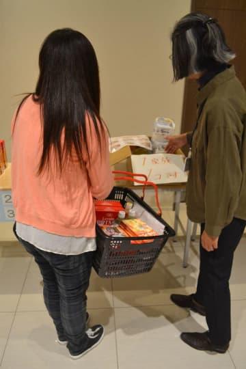 スタッフから説明を受けながら食料品を籠に収める利用者(左)=10月21日夜、富士見市鶴瀬東の鶴瀬駅前メモリードホール(画像の一部を加工しています)