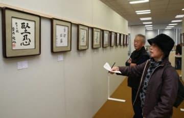 お気に入りの作品を品定めする来場者たち=山陽新聞社9階大会議室