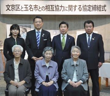金栗四三の3人の娘(手前)を立会人に、協力協定を結んだ東京・文京区の成澤廣修区長(後列左から2人目)と玉名市の蔵原隆浩市長(同3人目)=玉名市