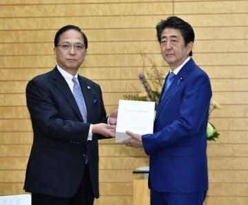 会計検査院の2018年度決算検査報告を森田祐司院長(左)から受け取る安倍首相=8日午前、首相官邸