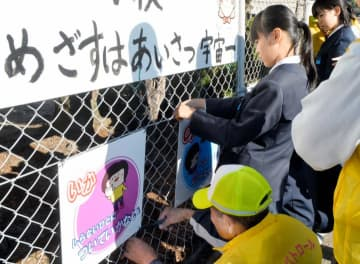 防犯プレートを設置する児童ら
