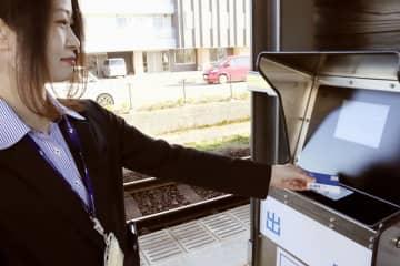 システムの実証実験で電子マネーカードを福井鉄道清明駅の簡易改札機にかざす女性=8日午後、福井市