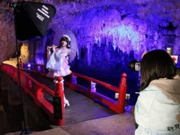 ライトアップされた満奇洞内で撮影を楽しむコスプレーヤーとカメラマン