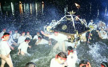 川岸までみこしを担ぎ、威勢よく水を掛け合う川組の男衆=8日、豊後高田市の桂川