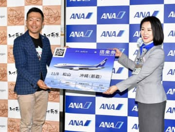 松山―沖縄線の航空券を受け取る阿部一大さん(左)=8日午前、松山市南吉田町