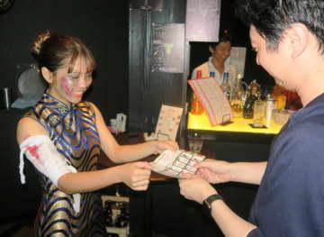 ゾンビの仮装をして来客にスタンプカードを渡すバーのスタッフ(左)=佐世保市常盤町