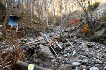 土砂崩れが起きた日航ジャンボ機墜落事故現場のスゲノ沢。岩や木、金属製の足場が押し流され、墓標の並ぶ斜面もえぐられていた=8日午後0時35分、上野村楢原