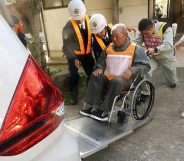 原子力総合防災訓練で、車いすのまま車両に乗り込む人=9日午前、松江市