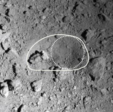 小惑星りゅうぐうの人工クレーター。実線部分が15メートルの範囲、点線は金属弾が直接当たったとみられる10メートルの範囲(JAXAなど提供)