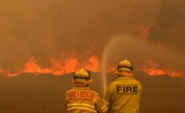 オーストラリア東部ニューサウスウェールズ州の山火事で消火に当たる消防士ら=9日(ロイター=共同)