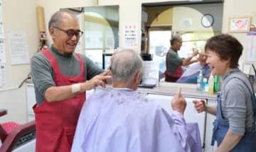 和やかな雰囲気で常連客の髪を切る松浦邦晴さん(左)。店を年内で畳み手話言語条例の普及に力を注ぐ=6日午後、宮崎市
