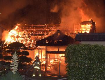 消火活動する消防隊員=9日午後6時10分ごろ、水戸市元吉田町