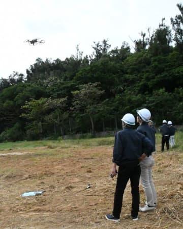 ドローンを操縦して周辺の状況を確認するスタッフ=5日、うるま市・浜比嘉島の旧比嘉小学校