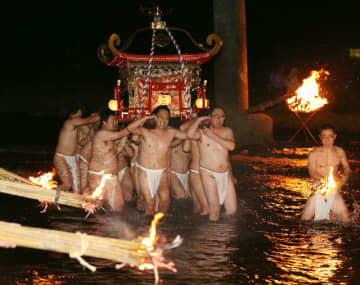 みこしを担いで緒方川を渡る締め込み姿の男衆=9日夜、豊後大野市緒方町