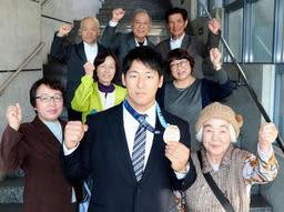 世界選手権の金メダルを手に、飛躍を誓う山本俊樹(中央)と、母芳江さん(左端)や地元住民ら支援者=三木市役所