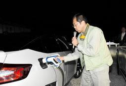 施設内につなぐコードを、電気自動車に差し込む神戸市職員=北区大沢町中大沢