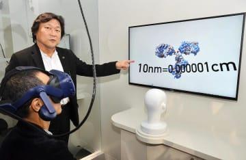 タンパク質に関するVR展示。ゴーグル装着者には360度の視野で映像が広がる=8日午前、松山市文京町の愛媛大ミュージアム