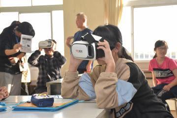 ARの技術で幻視の症状を体験する児童。ゴーグルでのぞく光景には、人が浮かび上がっている=8日、龍ケ崎市立大宮小