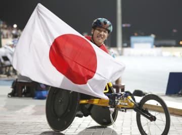 男子400メートル(車いす)で優勝し、日の丸を掲げる佐藤友祈。東京パラリンピック代表に内定した=ドバイ(共同)