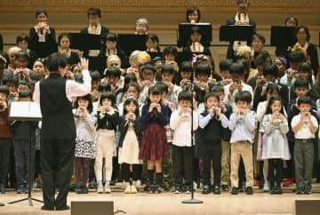 10日、ニューヨークで、黒坂黒太郎さん(左手前)の指揮でコカリナを演奏する日本人学校の生徒たち(共同)
