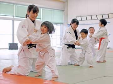 子どもたちと打ち込みをする櫻葉倶楽部のメンバー=長崎市、長崎女高柔道場
