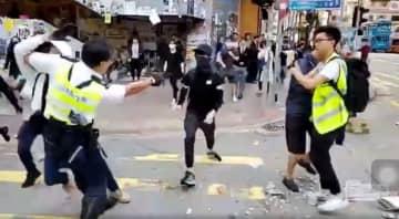 11日、香港で黒シャツとマスク姿の若者(中央)に銃を向ける警官(香港メディア「立場新聞」のウェブサイトより・共同)