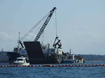 運搬船から土砂を台船に積み替える作業が進んだ=11日、名護市辺野古・米軍キャンプ・シュワブ沿岸