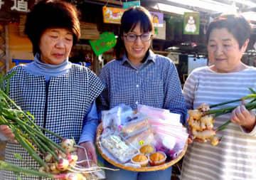 収穫されたショウガとマフィンや漬物などの加工品をPRするプロジェクトのメンバーたち(京都府南丹市八木町室河原)