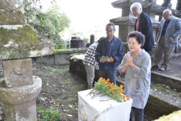 墓前に花をささげ、手を合わせる参列者たち