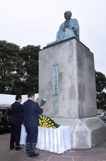 渋沢栄一の銅像にキクの花を手向ける参列者=JR深谷駅前