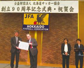 鈴木会長から感謝状を贈られた刀祢光夫室蘭民報社取締役営業局長(左)