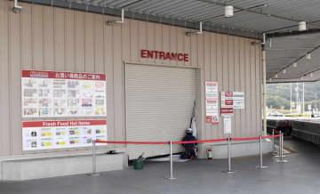 車が突っ込んで壊れた大型スーパー「コストコ北九州店」のシャッター=12日午前9時57分、北九州市八幡西区