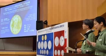 造幣局のスクリーンに映し出された野見宿禰像とギリシャの女神像の記念貨幣=8日、大阪市北区