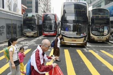 香港・九竜地区の繁華街では、前日のデモの影響でタイヤがパンクしたバスが道路をふさいでいた=12日(共同)