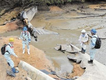 長柴山ため池の決壊箇所を調査する国や県の担当者ら=10月23日