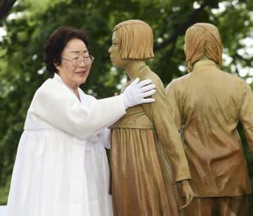 ソウル中心部の南山に設置された慰安婦問題を象徴する少女像を抱く元慰安婦の李容洙さん=8月(共同)